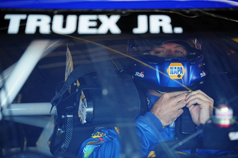 Martin Truex Jr., driver of the #56 NAPA Auto Parts Toyota, sits in his car in the garage area during practice for the NASCAR Sprint Cup Series Quicken Loans 400 at Michigan International Speedway