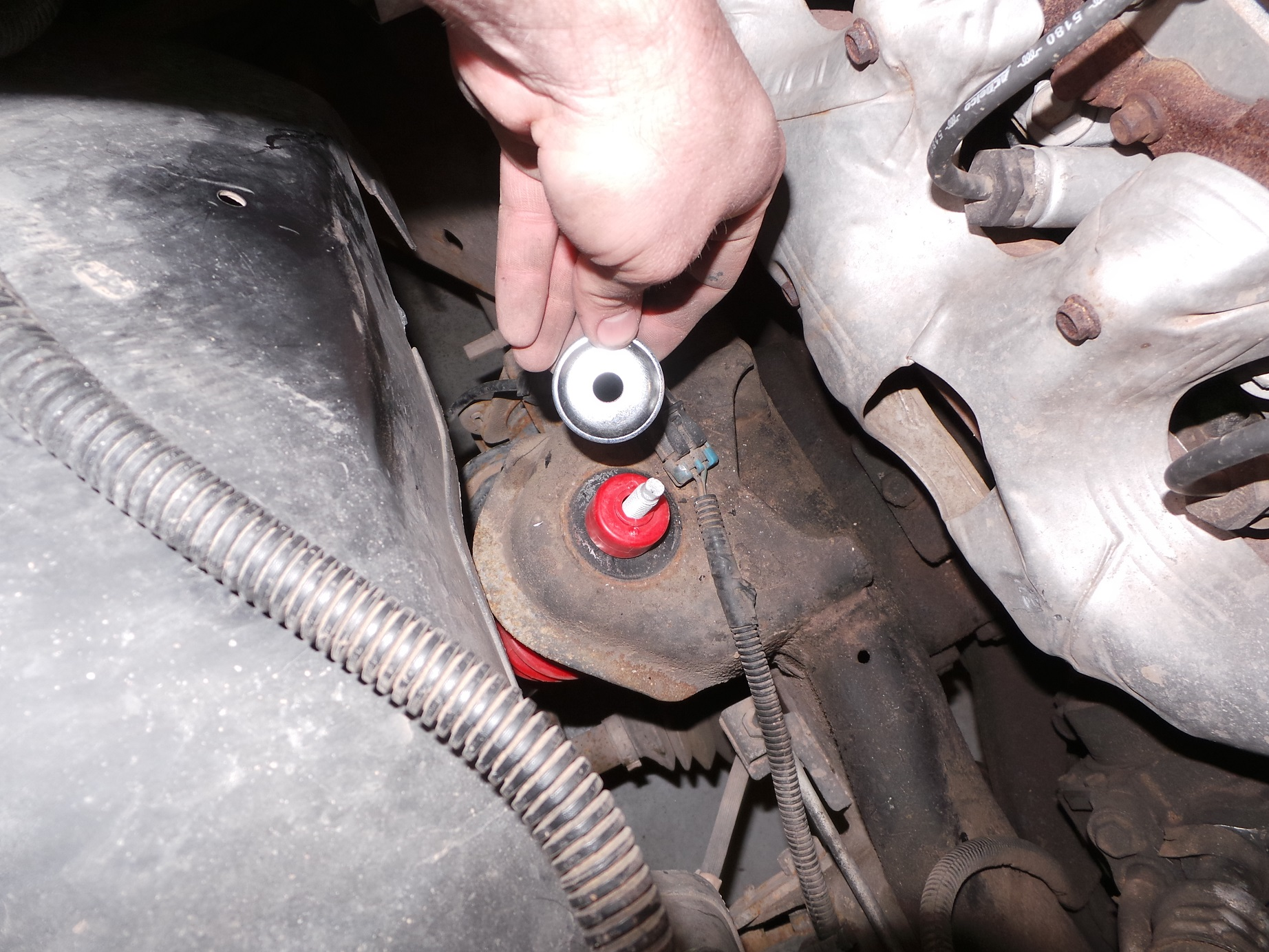 There are 2 bushing, 2 washers and a nut for the upper mount. Make sure the bushing is centered in the hole.