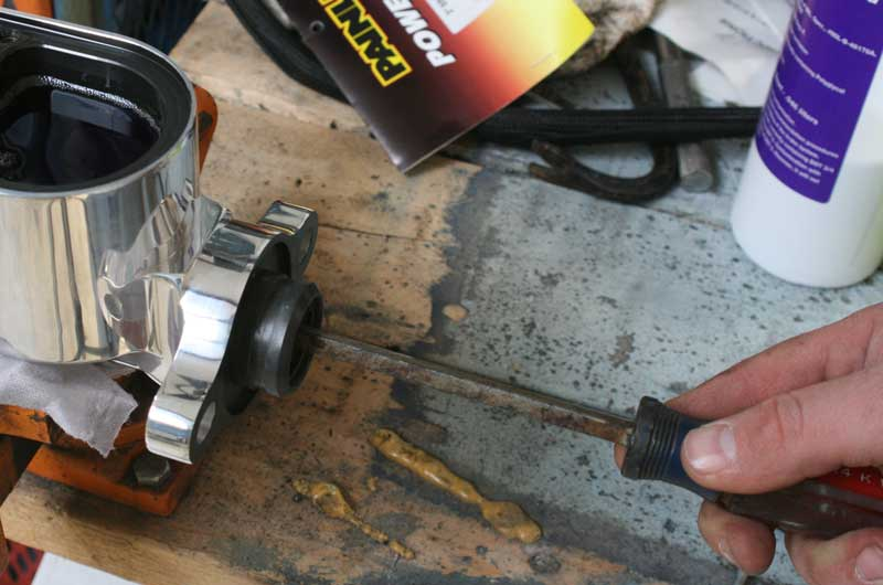 Using a screwdriver or ratchet extension, slowly operate the piston in and out to push fluid through the lines.