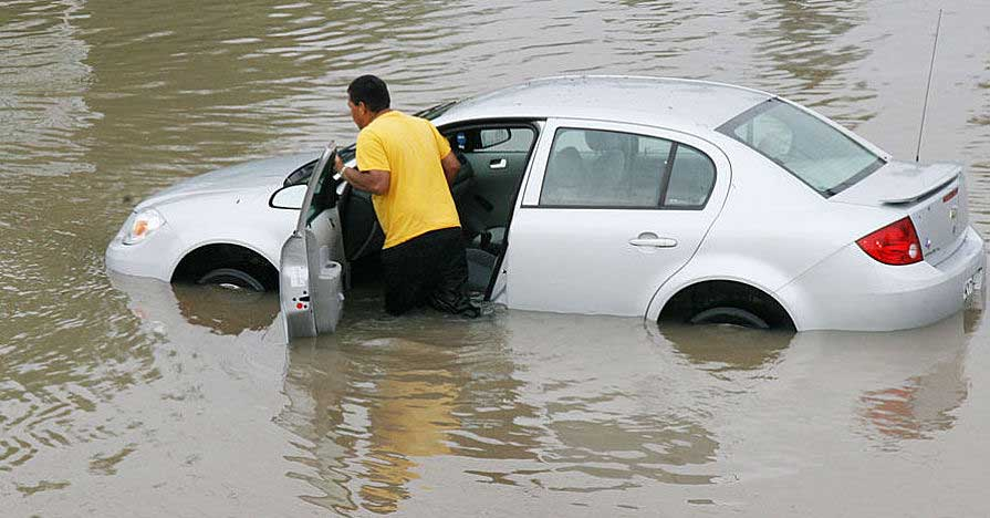 Man pushes flooded car through deep water.