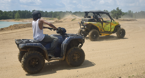 A pair of ATV enthusiasts prepare to traverse the sandy terrain of a favorite ATV park.