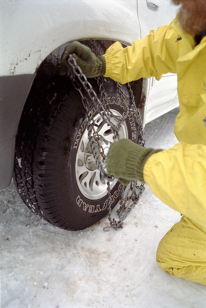 A man puts chains on his tires.
