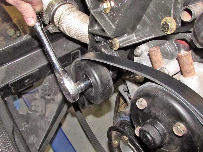 Using a ratchet and socket (some tensioners do not require a socket, just the ratchet head), release the tension and hold in place.