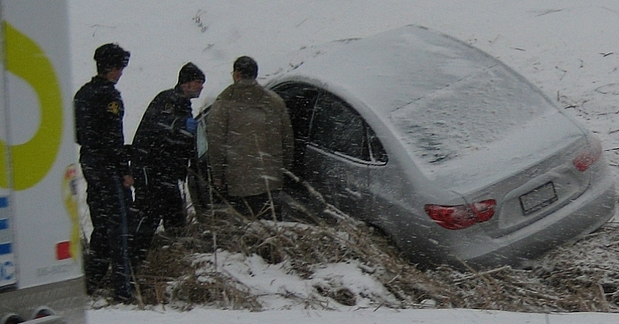 A car stuck in a ditch with emergency help present