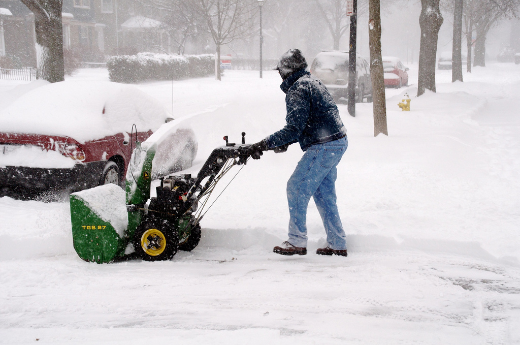 Man using snow blower in storm