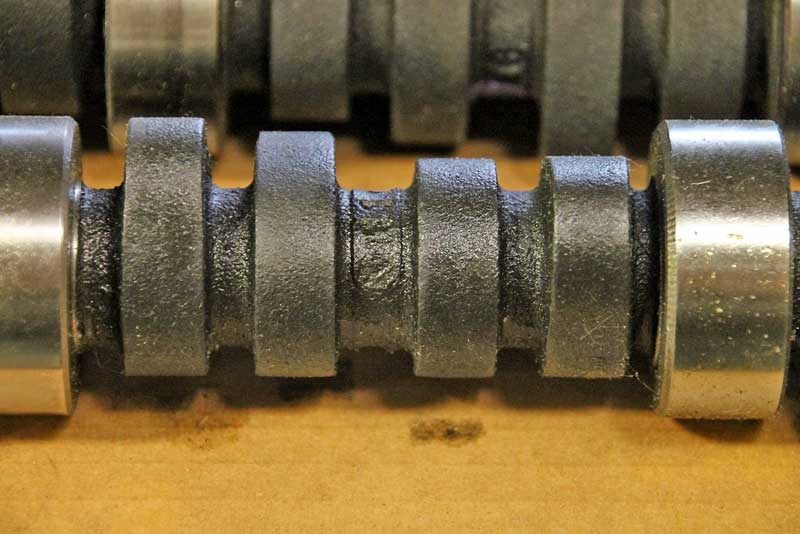 This a cast camshaft. You can clearly see the rough casting and each lobe. This requires machining to set the final profile.