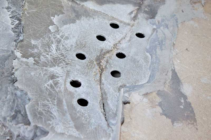 "After cleaning the area with an 80-grit sanding pad on a die-grinder, a series of holes were drilled into the body on either side of the crack. These are ½"" holes. It is also a good idea to drill the ends of the crack to stop its progress. The holes will connect both sides of the repair, locking it all in place."