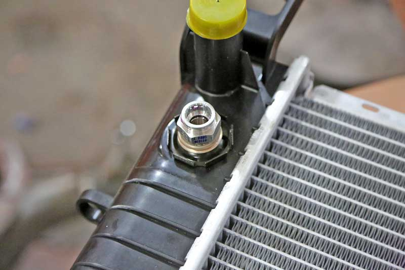 On the side of the tank, most vehicles have fluid ports for transmission fluid. They look like this and use wire retainer clips to hold the line in place.
