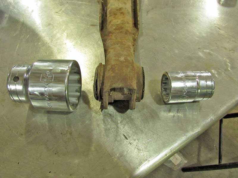Choose two large sockets, one that fits over the large end of the bushing (where it will be pushed out), and a smaller one to match the outside shell on the other side. The smaller socket needs to fit inside the hole for the bushing in the arm.