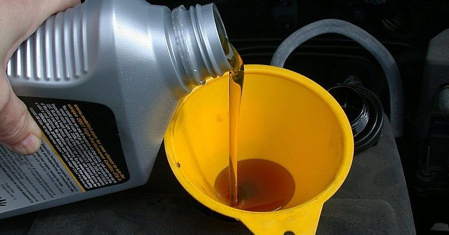 A vehicle's oil reservoir being filled with a funnel. A closer analysis of the numbers on the bottle can tell you more about the oil weight.
