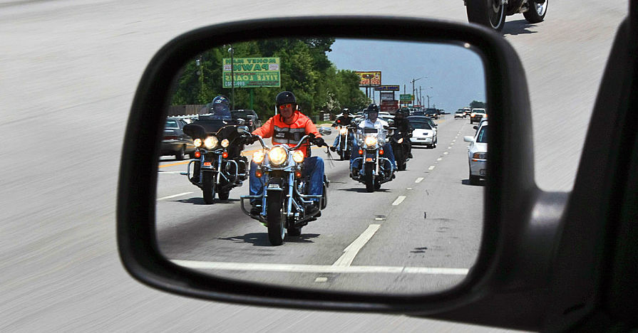 A side mirror of a car, reflecting motorcyclists
