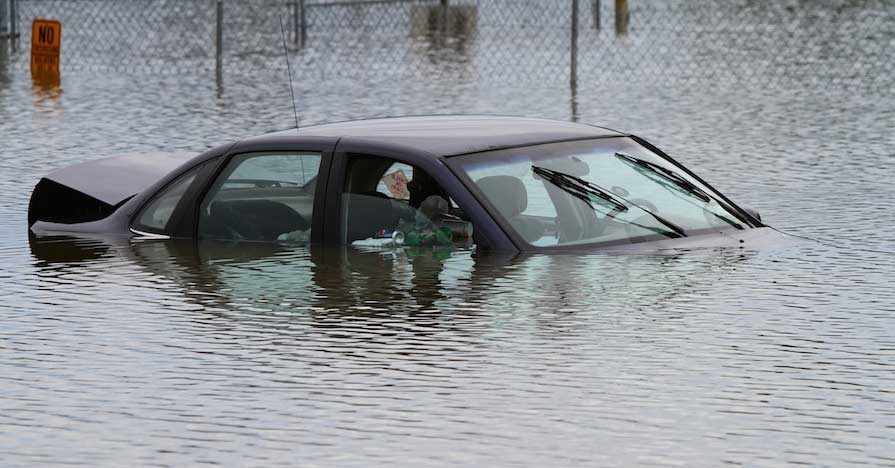 A flood-damaged car almost completely submerged in flood waters.