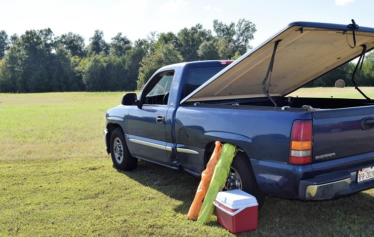 A truck camping setup: A hard cover is raised over the bed and camping supplies lean against the back wheel.