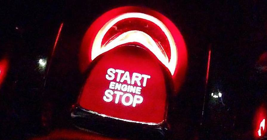 A car start button at night, illuminated in red, in a modern automobile.