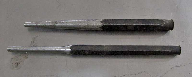 The top punch is a taper punch, the lower one is a drift or pin punch. The taper punch is used to start a pin moving, and the drift punch is for actually driving it out.
