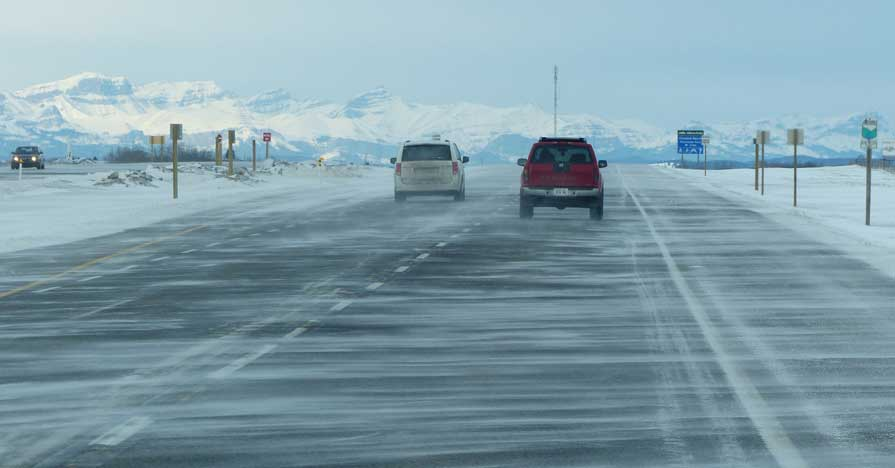A highway in the wintertime speckled with cars; snow-capped mountains are pictured in the distance.
