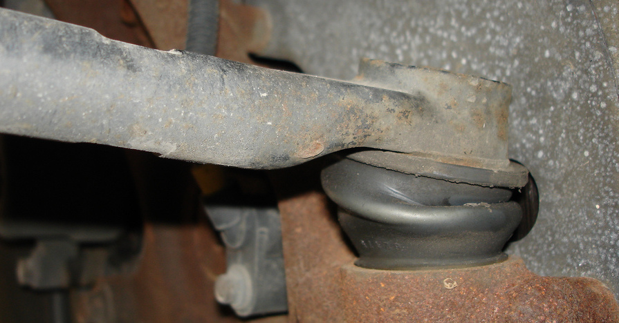 A tie rod end under the wheel of a car.