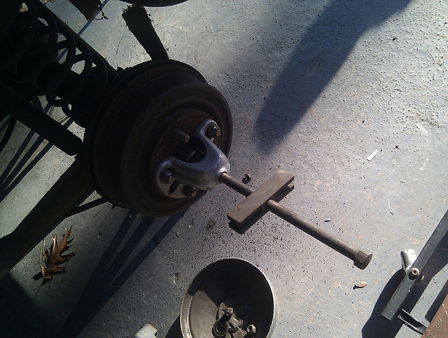 Removing a rear brake drum from a vehicle.
