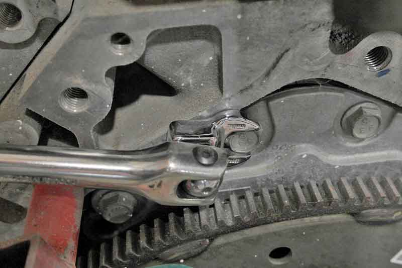 Instead of that absurd wrench on wrench action, use a crowfoot and a ratchet or breaker bar to get the job done.