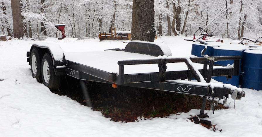A snow-covered trailer ready for winter towing.