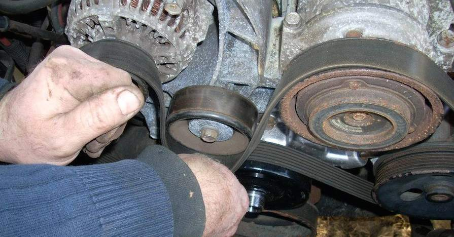A mechanic replaces a serpentine belt inside a vehicle.