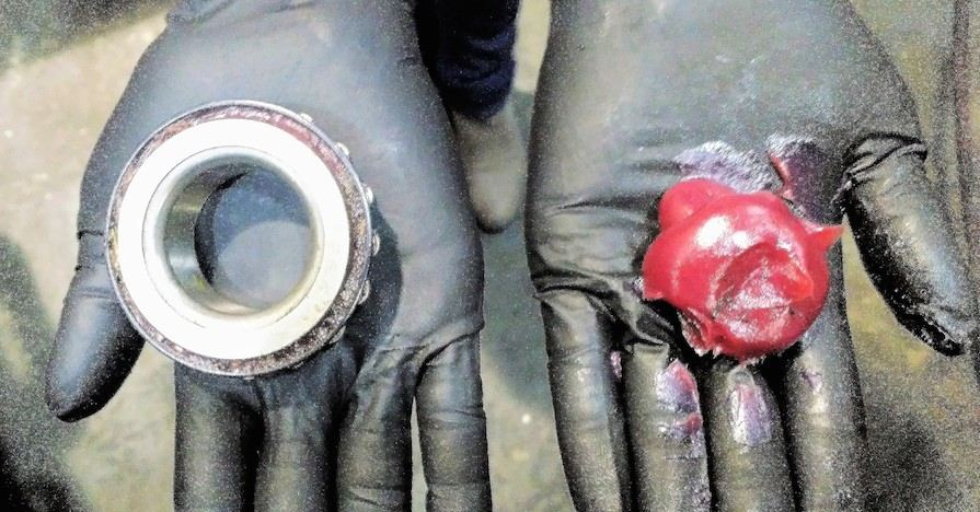 A gloved hand holds a car wheel bearing, ready to be repacked.