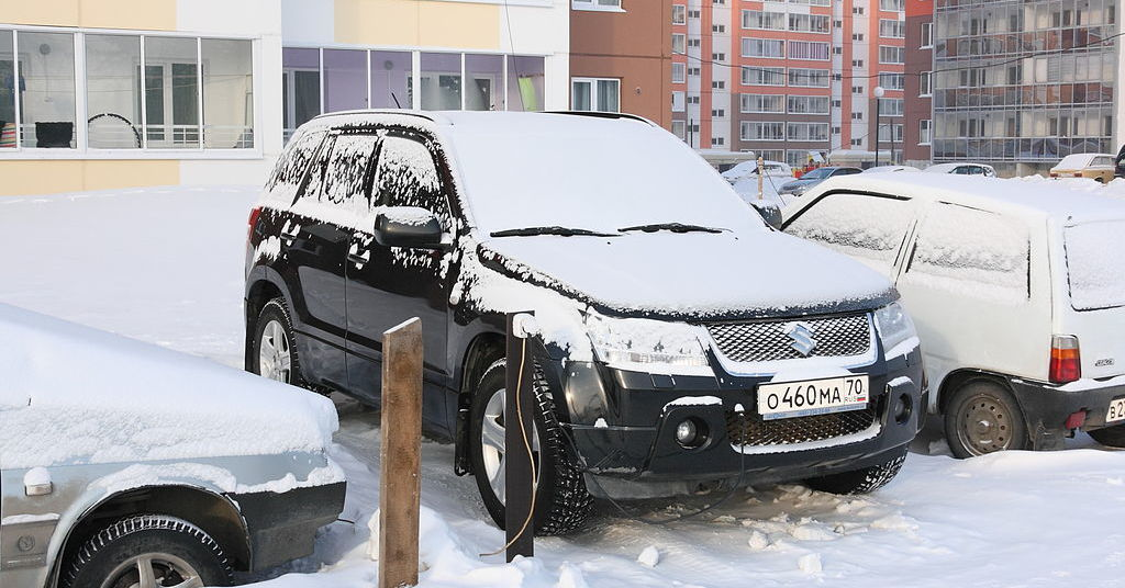 A Suzuki is parked in the snow and connected to a power outlet to power a diesel block heater.