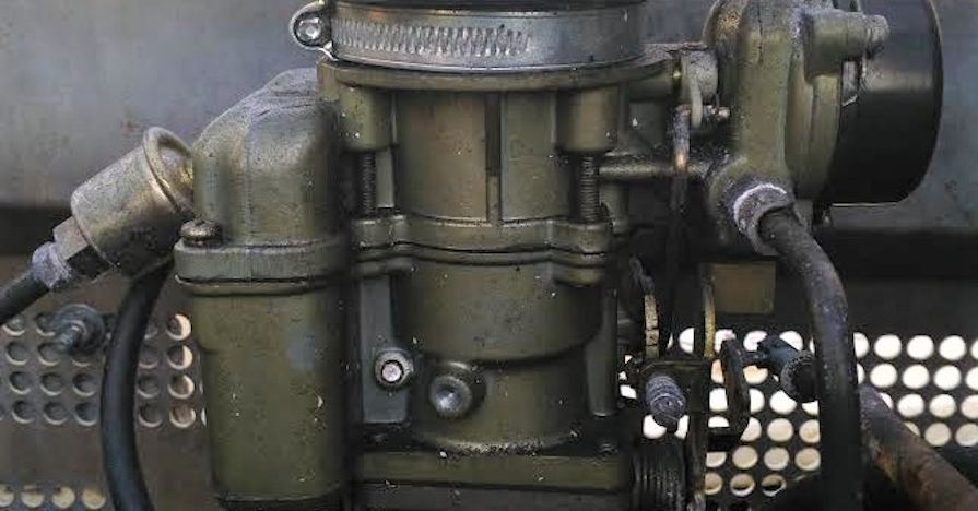 A close-up of a carburetor, a large, metal drivetrain component in older vehicles.
