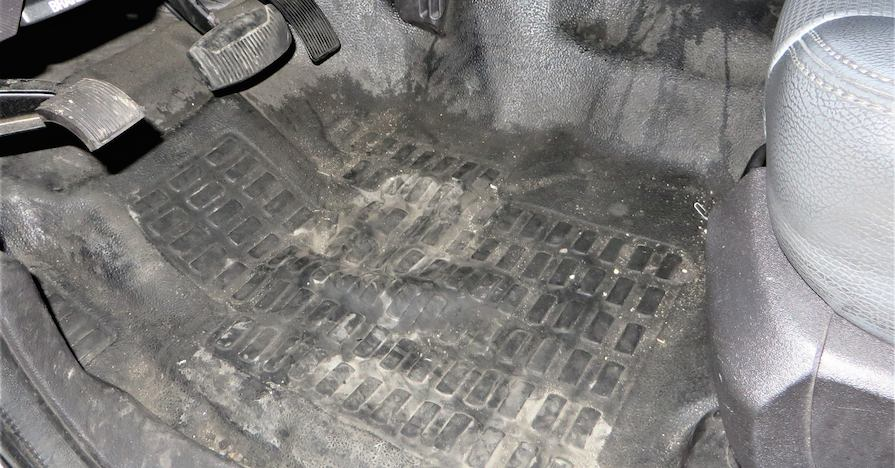 This car floor has a muddy mat.