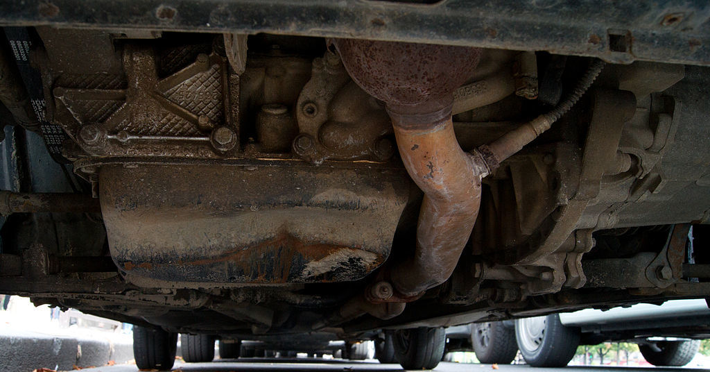 A rusted, cracked oil pan in the undercarriage of a car.