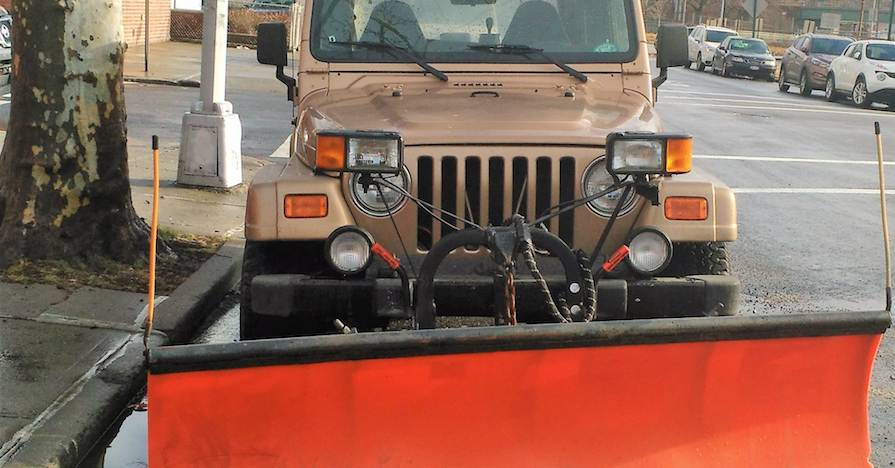A Jeep Wrangler parked on the street, outfitted with a plow.