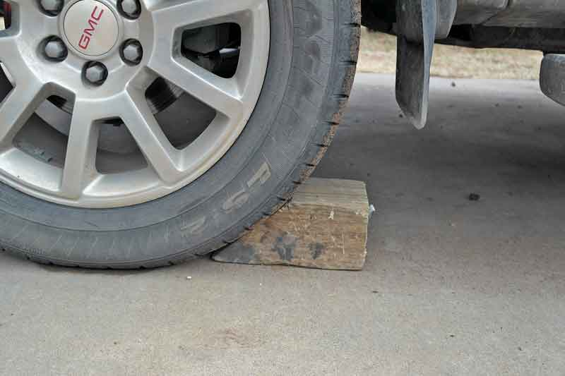 You can buy fancy wheel chocks (get quality larger ones, bigger is better), but in a pinch, you can use a nice 4x4 with a 45-degree angle cut on the end.