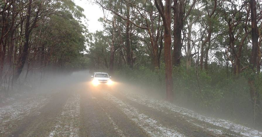 A vehicle is driving in a hailstorm on a country road.