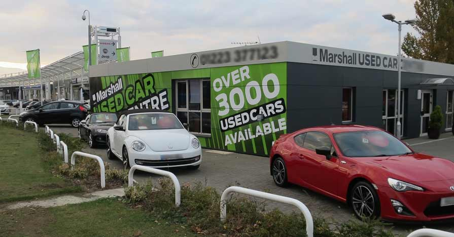 A variety of used cars lined up for sale in a lot.