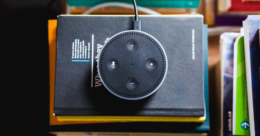 An Amazon Echo Dot sitting on a book.
