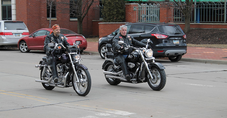 Two older men ride large motorcycles down a quiet city street, after having performed spring motorcycle maintenance.