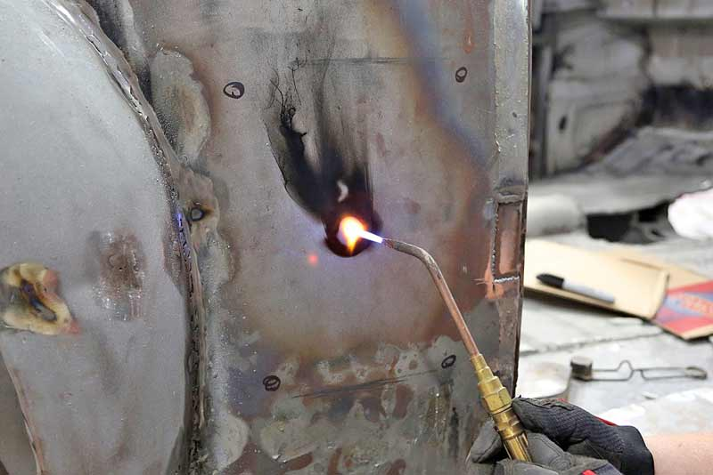 Using a rosebud torch tip, heat the center of the metal to be shrunk. You are looking for a nipple to form in the center.