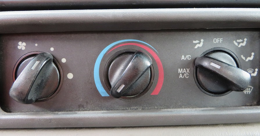 Climate control dials are pictured in a car dashboard.