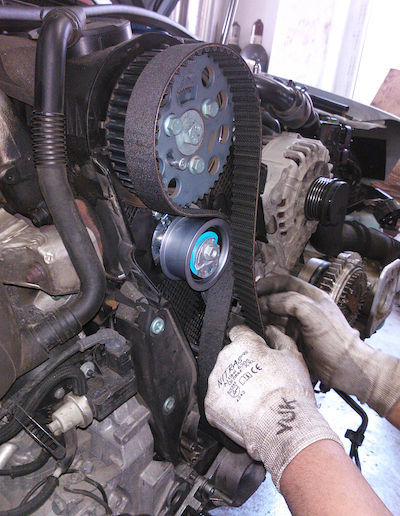 A mechanic replaces a broken timing belt.