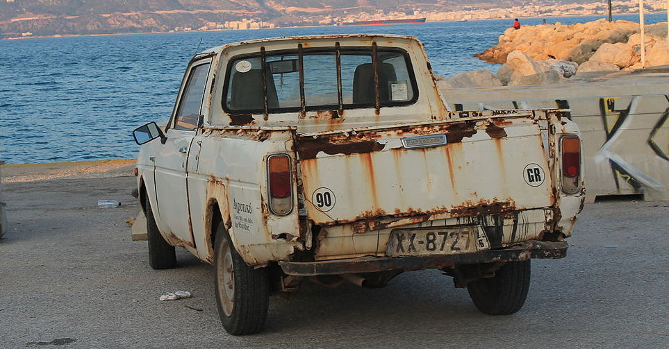 A severely rusted pickup truck is parked by a lake.