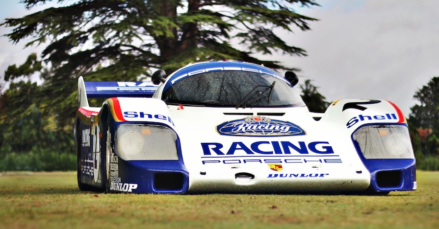 "A race car that reads ""Racing Porsche"" is parked in a field by a tree, filled with high-performance brake fluid."