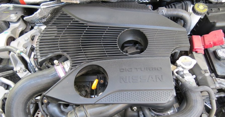 An interference engine is under the hood of a Nissan car.
