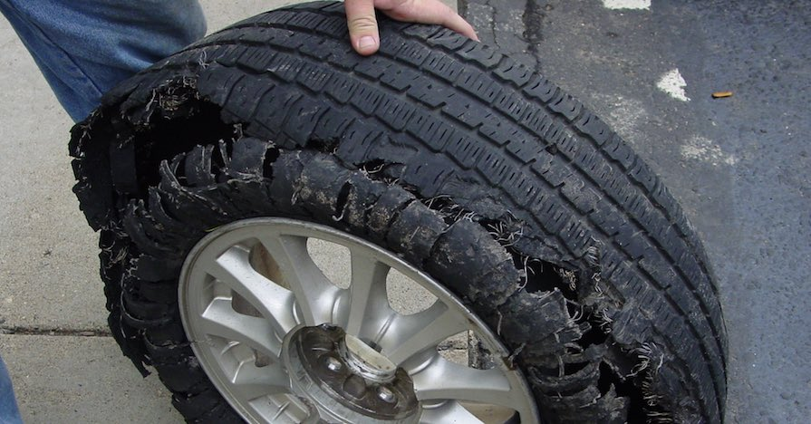 A man is holding a badly damaged tire upright on a sidewalk.