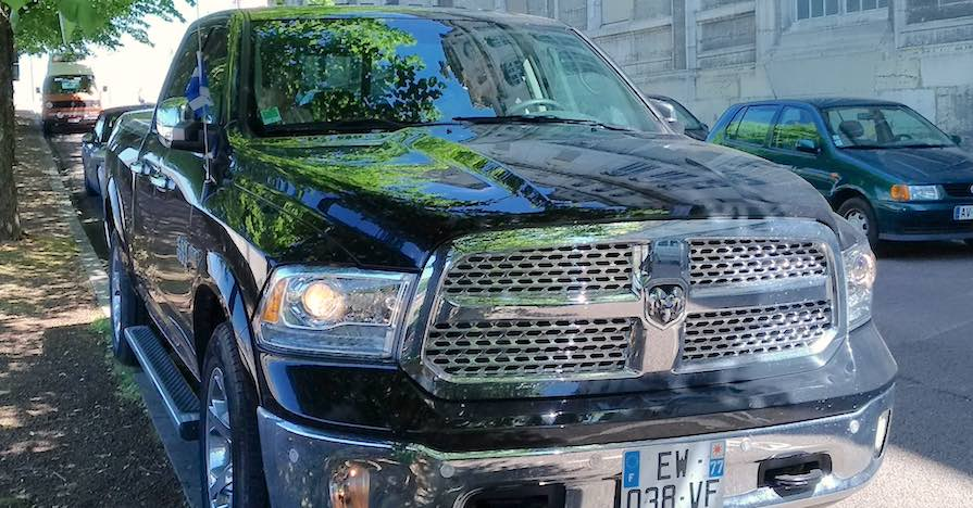 A Ram 1500 pickup truck is parked on a street.