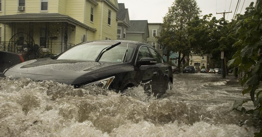 A sedan drives through welling flood waters.