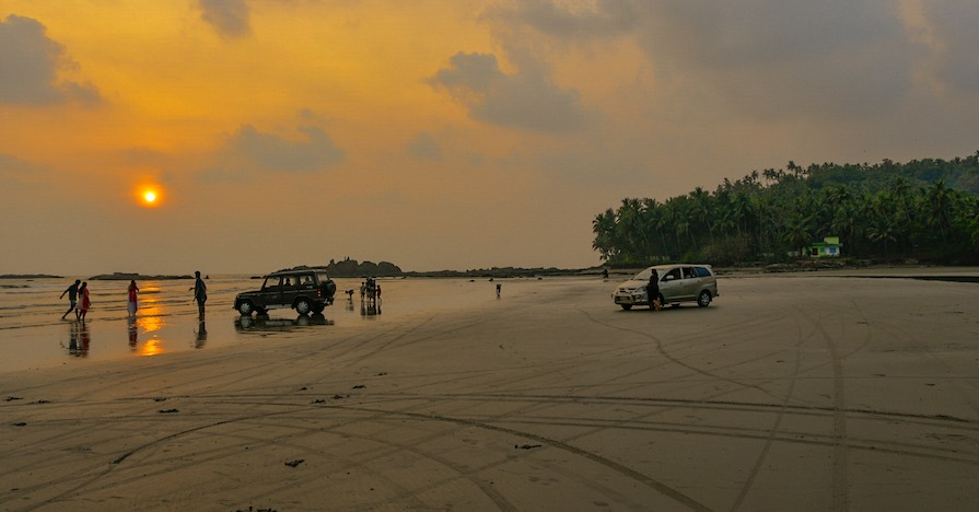 An off-road enthusiast is beach driving over a low tide, framing the vehicle with kicked-up water