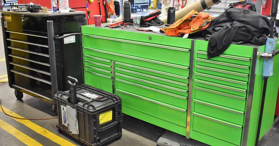 A variety of tool boxes that range in size and shape sit on a garage floor.
