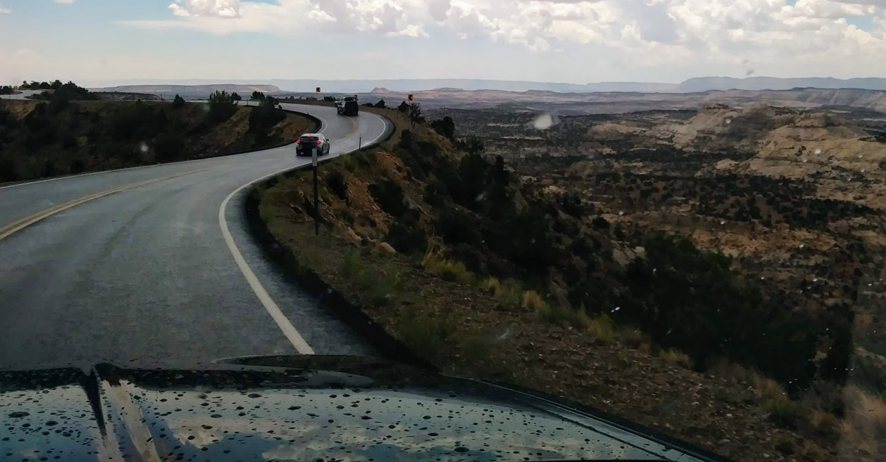 A car with lane assist drives down a winding country road in Utah.