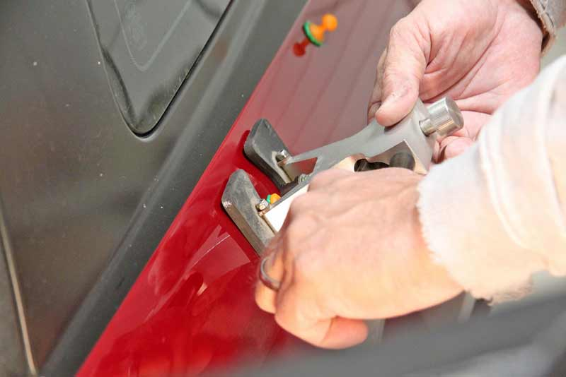 Using a special puller tool, the tech carefully pulled up each pin until the dent was gone. This is a delicate process.