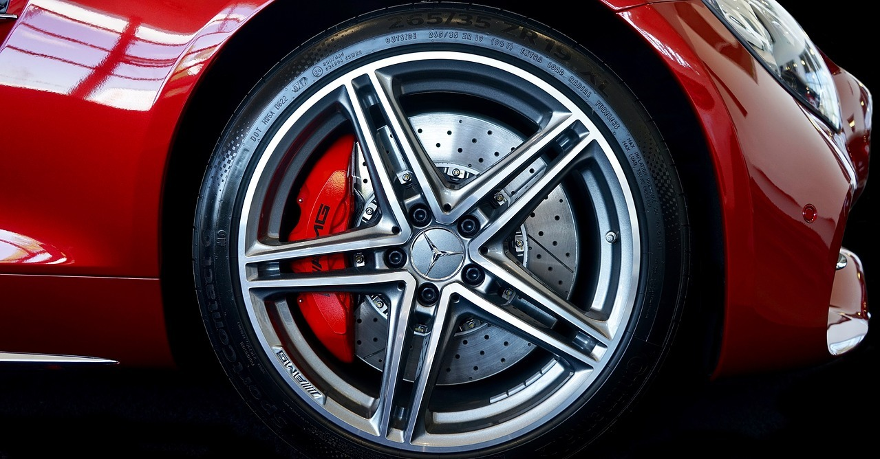 This brake caliper is on the wheel of a Mercedes-Benz sports car and is probably a fixed caliper.